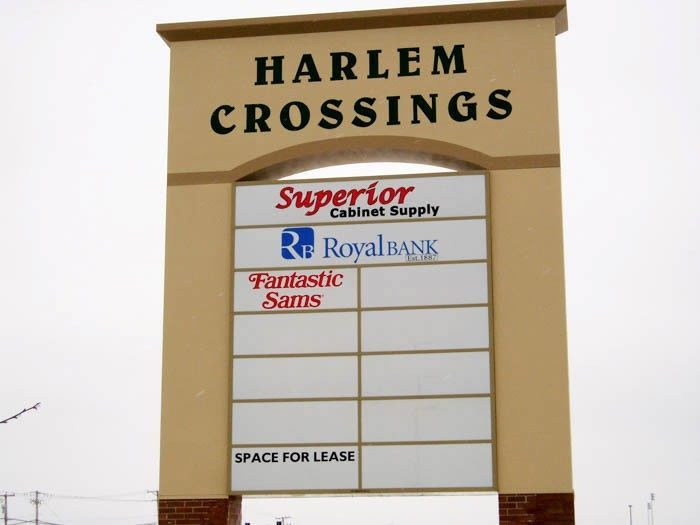 A monument sign with the names and logos of multiple businesses, representing how one can benefit from calling a Plainfield, IL sign company.