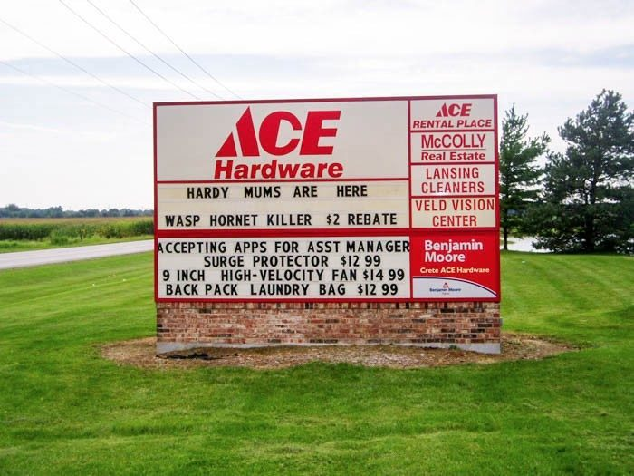 A monument, red and white sign in a grassy area, representing how one can benefit from calling a Plainfield, IL sign company.