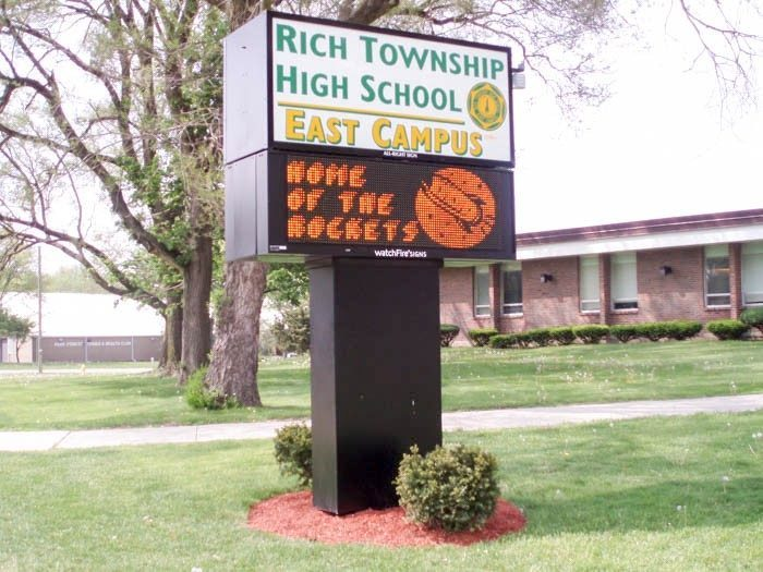 A tall digital sign outside of a school, representing how one can benefit from calling an Orland Park digital sign company.