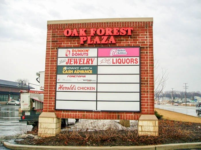 A monument sign with the names and logos of businesses in a parking lot, representing how one can benefit from calling a Tinley Park sign company.