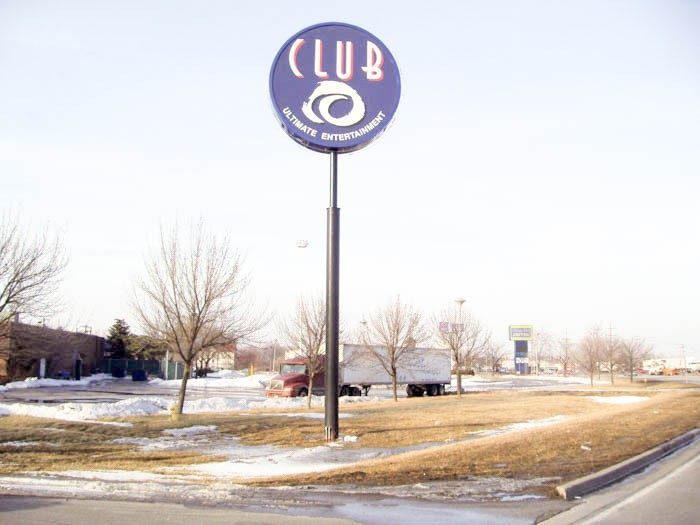 A monument sign with the name and logo of a business in a parking lot, representing how one can benefit from calling an Orland Park sign company.