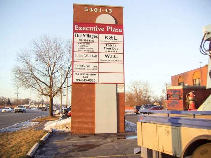 A large, monument sign with the names and logos of businesses in a parking lot, representing how one can benefit from calling a Chicago sign company.