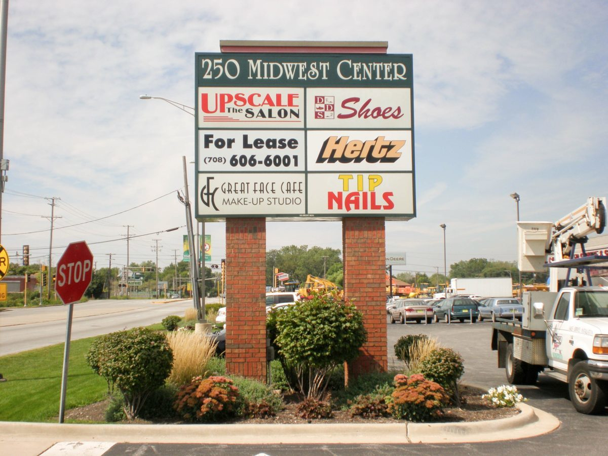 A monument sign outside a parking lot with a lot of names and logos of businesses, representing how one can benefit from calling a Schererville, IN sign company.