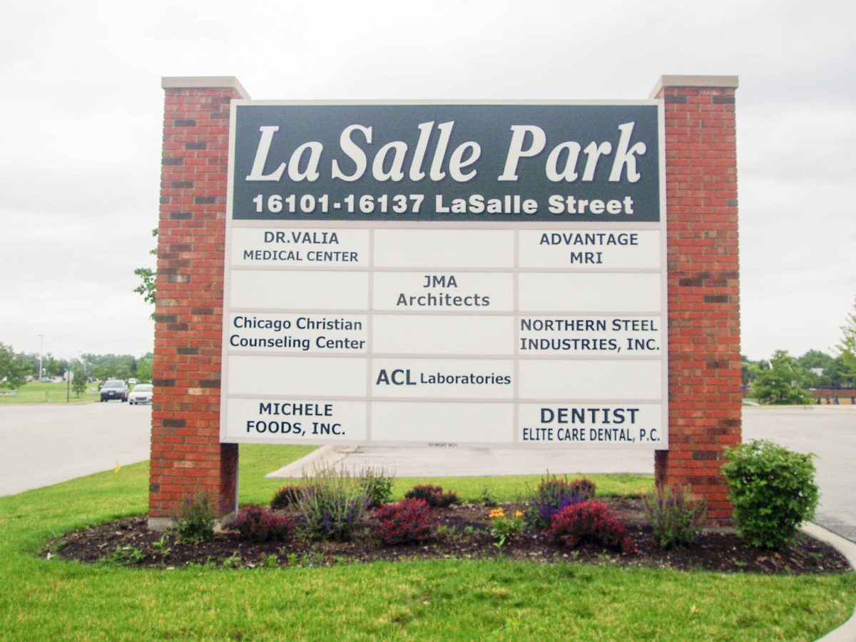 A monument sign in a parking lot with the name of the businesses, representing how one can benefit from calling a Chicago sign company.