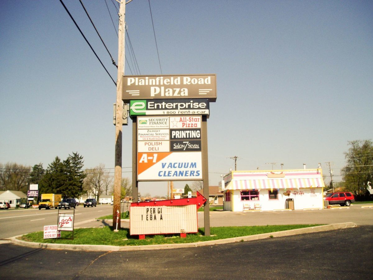 A monument sign with the names and logos of multiples business in a parking lot, representing how one can benefit from calling a Tinley Park sign company.