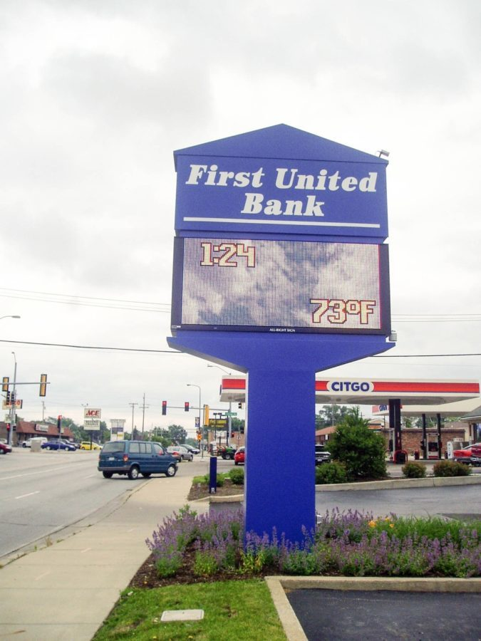 A large, blue, monument, digital sign for a bank in a parking lot, representing how one can benefit from calling a Tinley Park sign company.