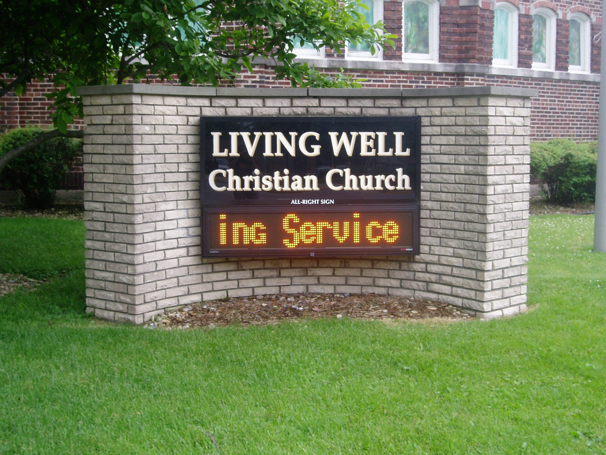 A monument, digital sign in a grassy area outside of a church, representing how one can benefit from calling a Merrillville digital sign company.