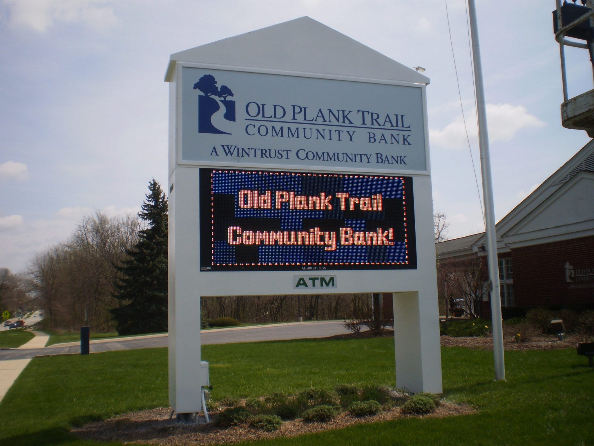 A white, outdoor digital sign for a bank, representing how one can benefit from calling a Joliet digital sign company.