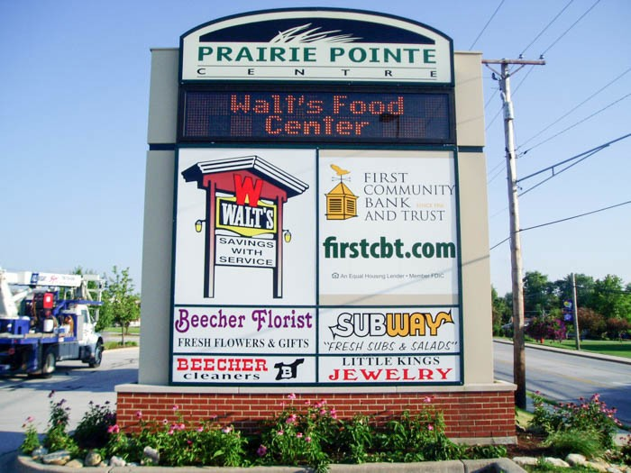 A monument sign with the names and logos of multiple business, representing how one can benefit from calling an Orland Park commercial sign company.