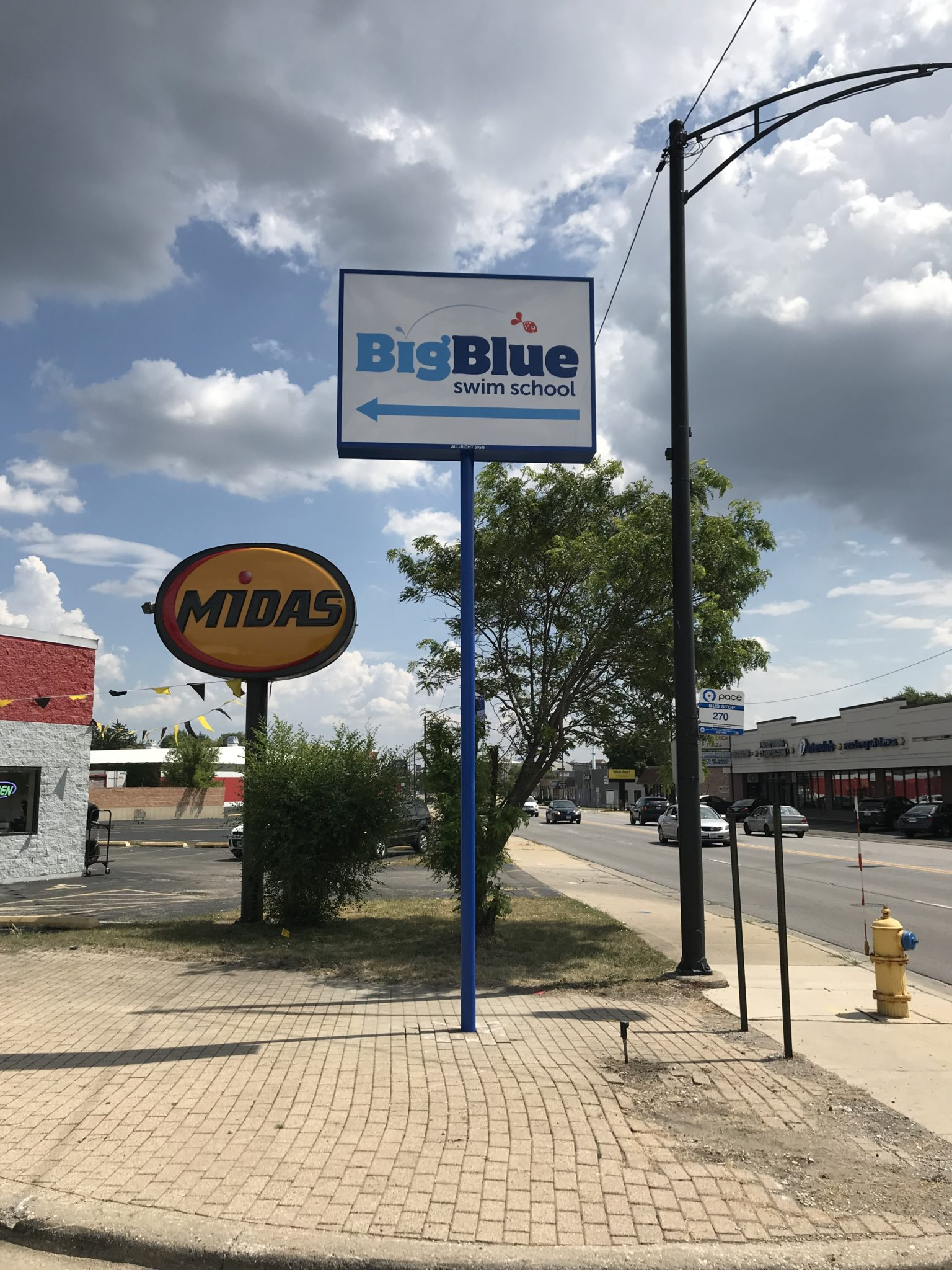 "A busy intersection with business, there are two big signs. One yellow that says ""Midas"" and a taller white one with blue letters that says "" Big Blue"", representing how one can benefit from calling the best Merrillville sign company."