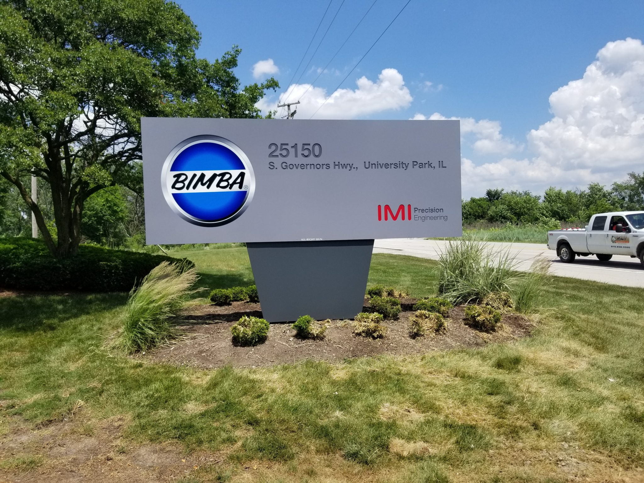 """Large picture of a garden with a gray and blue sign that says """"Bimba"""", representing how one can benefit from calling a Merrillville commercial sign company."""