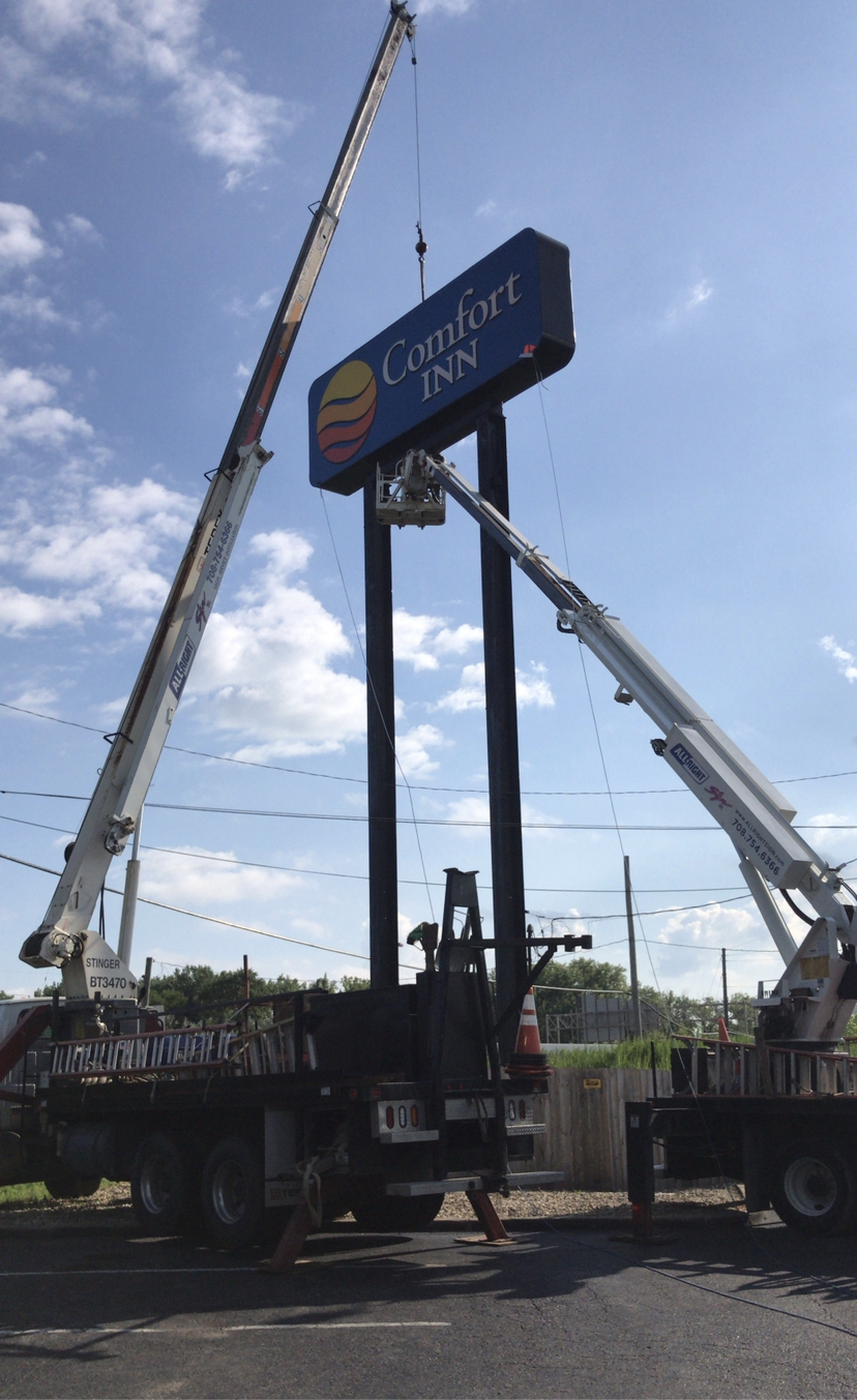 A tall and colorful sign being installed outside a hotel, representing how one can benefit from calling a commercial sing company in Tinley Park.