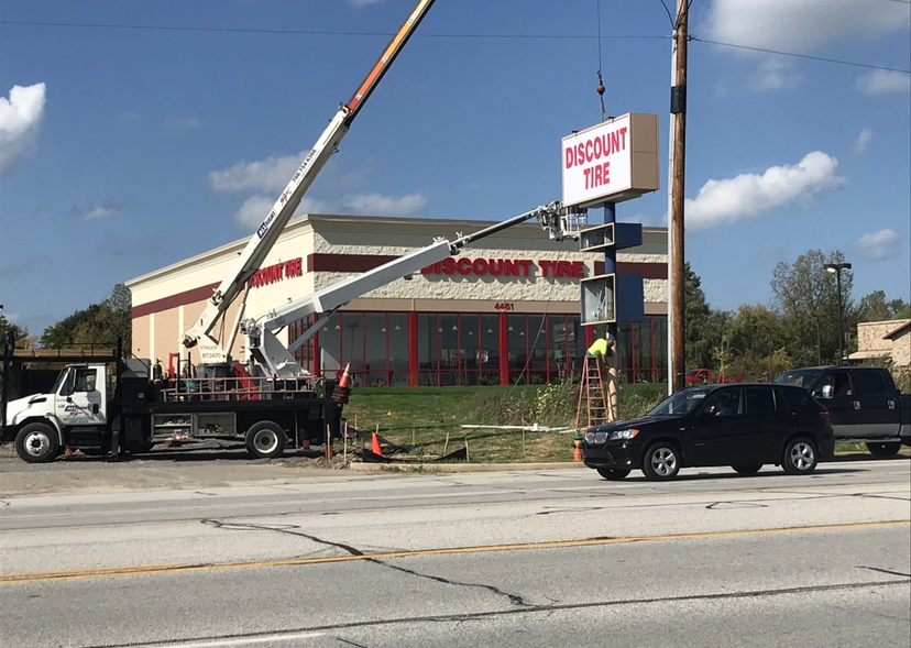 """The outside of a commercial business with a truck and a crew installing a new tall, white sign that says """"Discount Tire"""", representing how one can benefit from calling a Cook County, IL commercial sign installation company."""