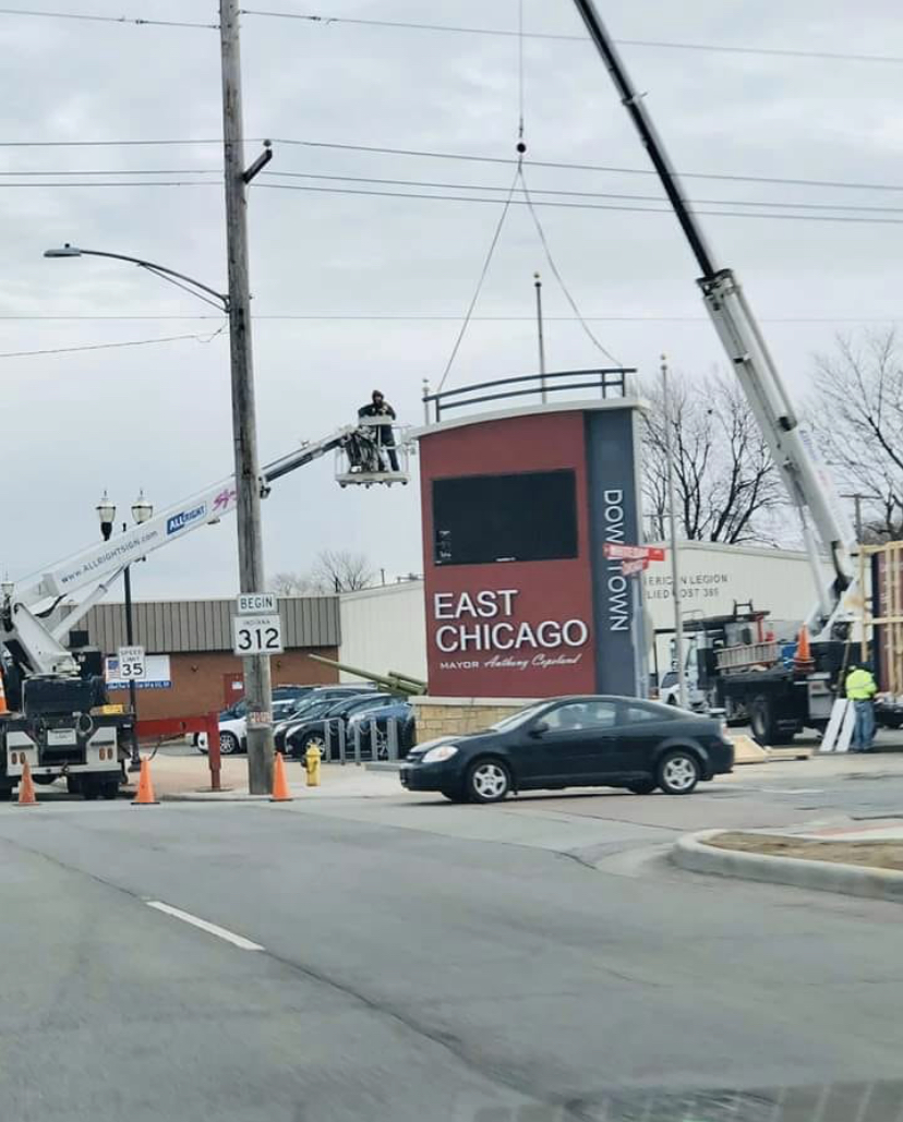 A brown and gray sign being setup outside of a busy intersection, representing how one can benefit from calling a Joliet commercial sign company.