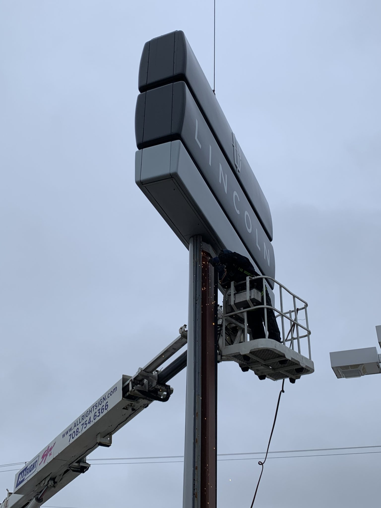 A crew installing a monument sign, representing how one can benefit from calling a Joliet sign installation company.