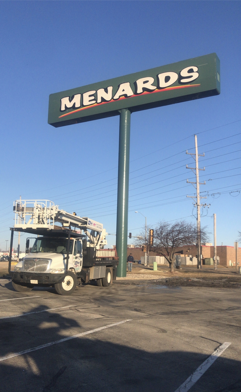 A truck in the parking lot of a business after fixing a sign, representing how one can benefit from calling a Tinley park commercial sign company.