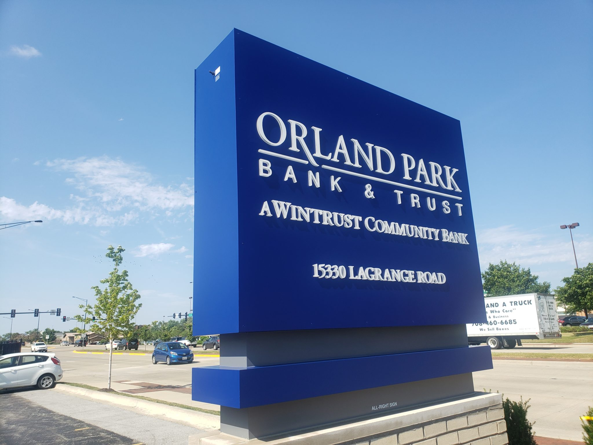 "A busy intersection with a blue sign outside a building that says ""Orland Park Bank & Trust"", representing how one can benefit from calling a Joliet monument sign company."