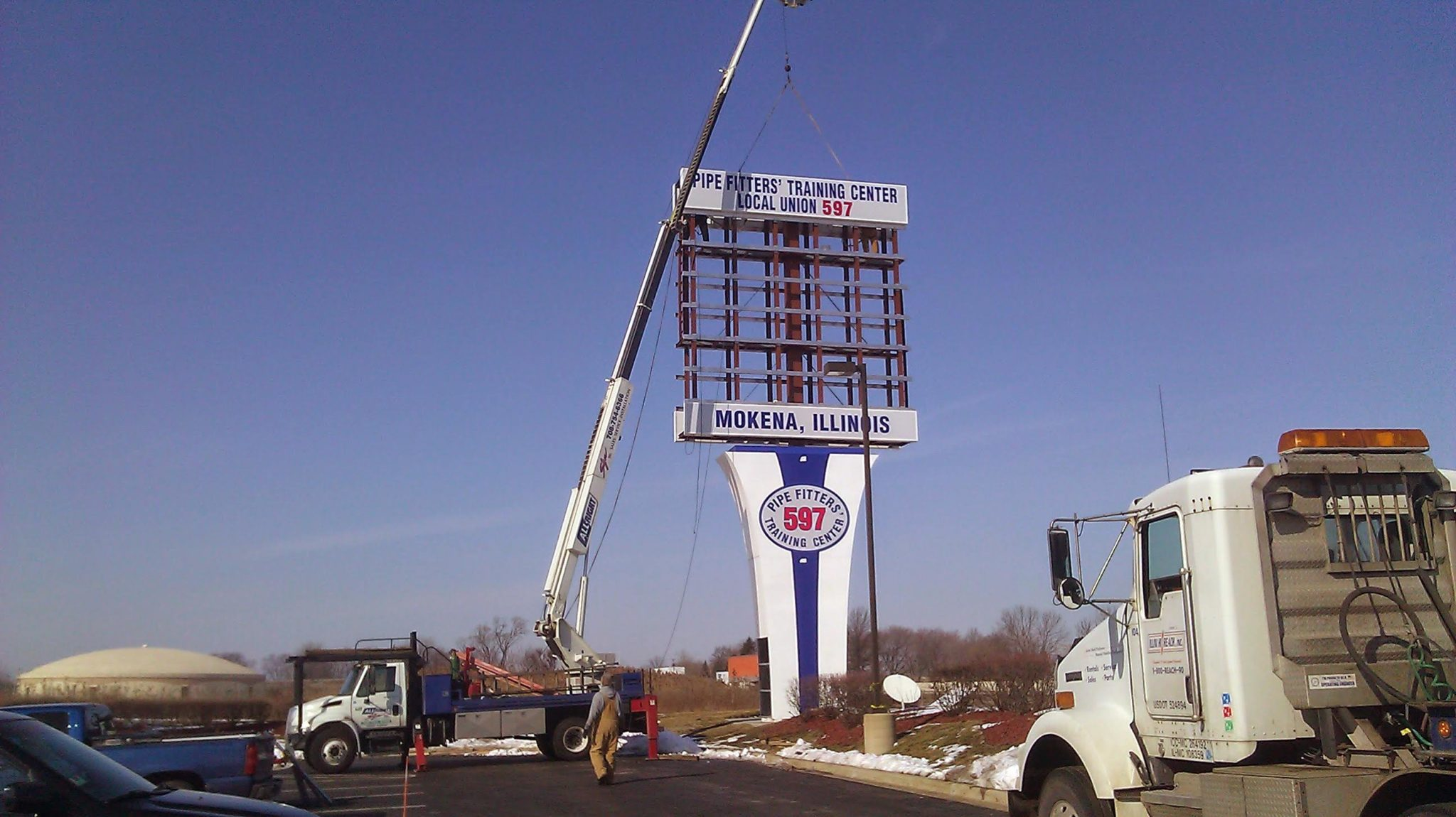 A tall, white sign being installed outside of a business, representing how one can benefit from calling a Joliet sign company.