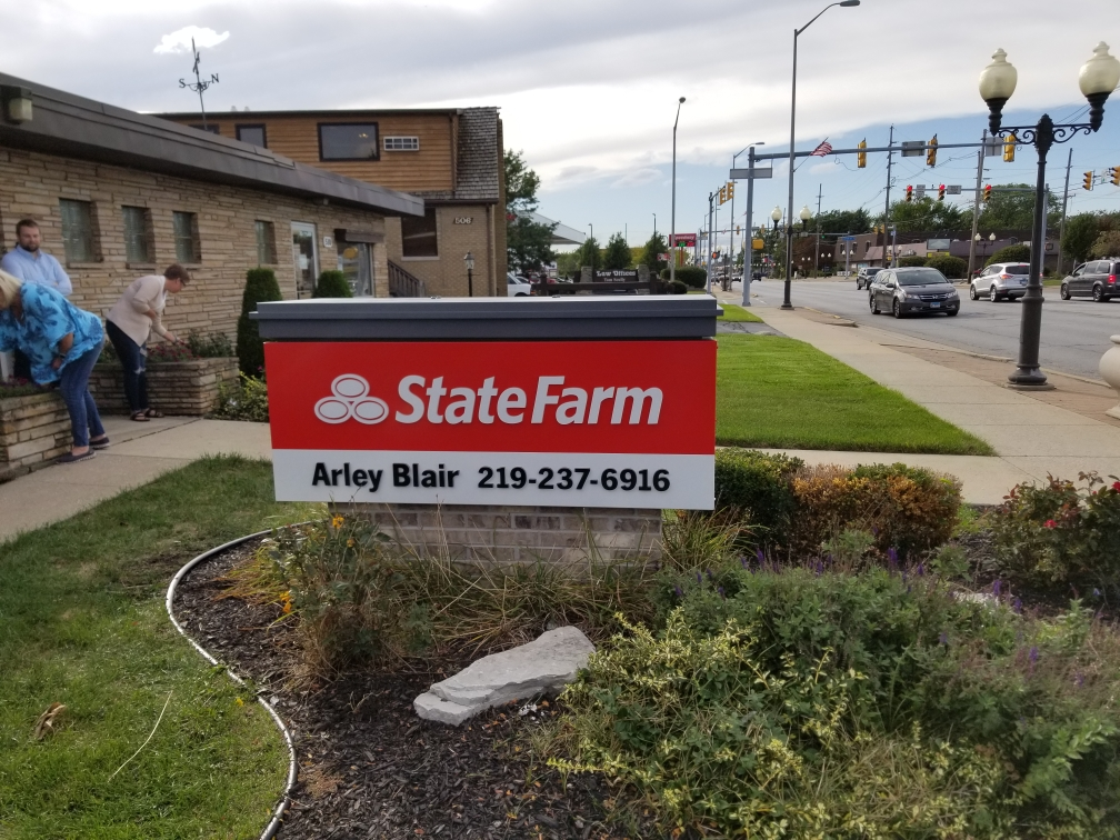 "A building outside of a busy street with a red sign that says ""State Farm"", representing how one can benefit from calling the best Chicago monument sign company."