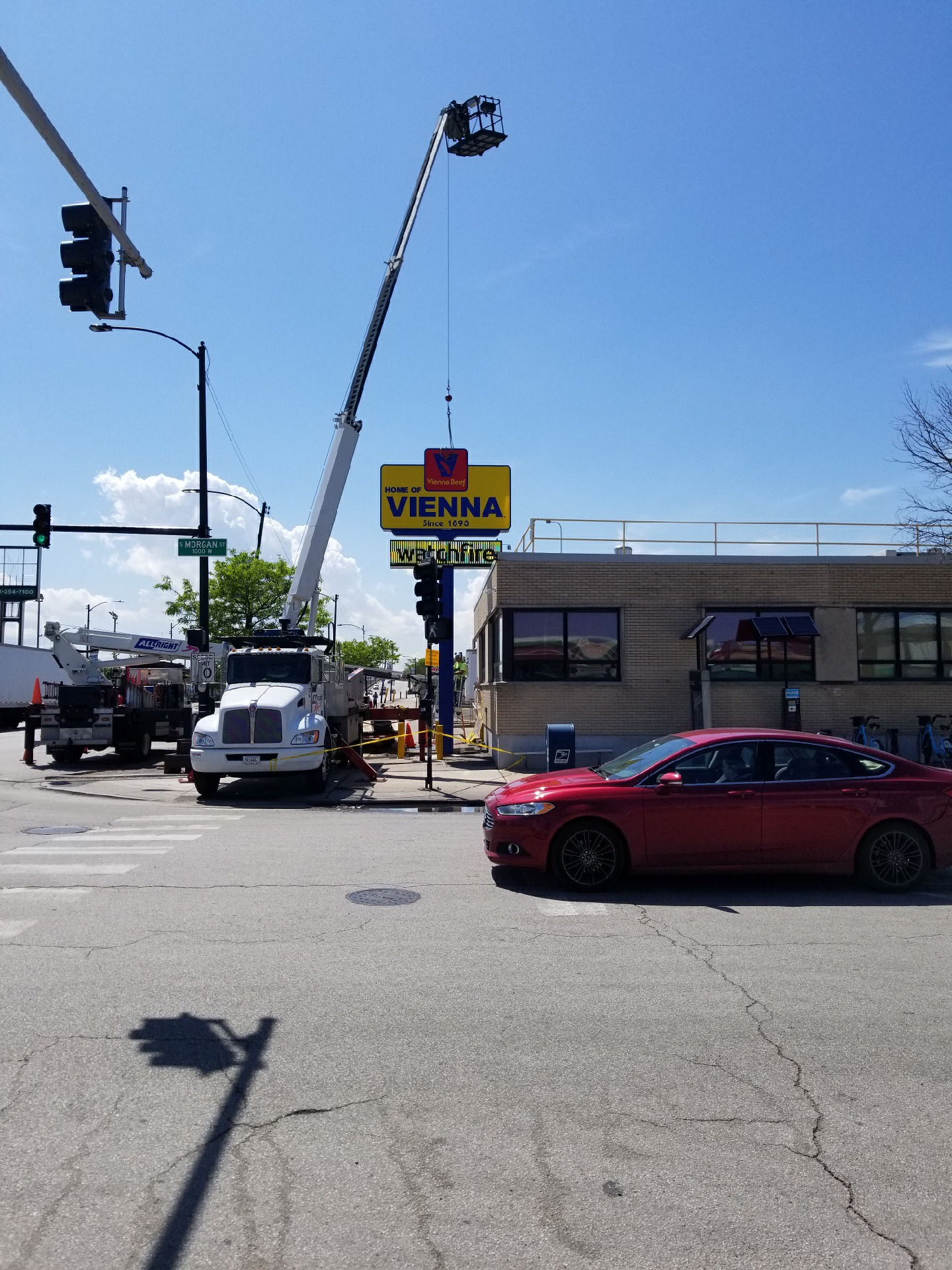Large picture of a street where a business is getting a new bright yellow sign installed, representing how one can benefit from calling a Merrillville sign installation company.